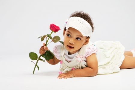 Lovely little girl with a rose lying on white background photo
