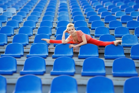 Beautiful sporty woman doing the splits on stadium photo