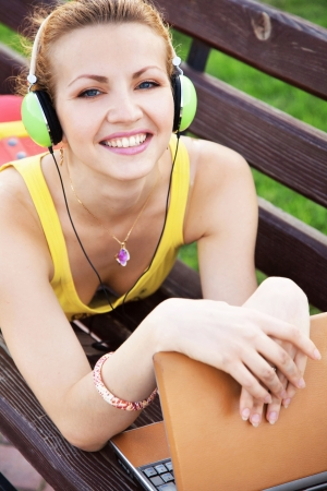 Young cheerful woman having rest in the park with laptop photo