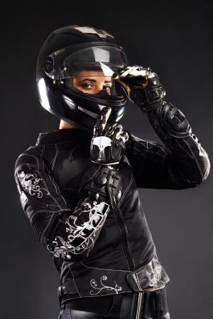 Mujer hermosa en traje de ciclistas contra bacground negro Foto de archivo