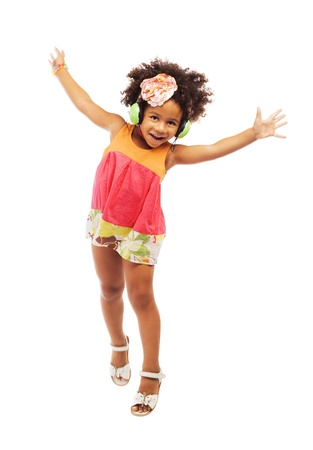 Joyful little girl in headphones is jumping