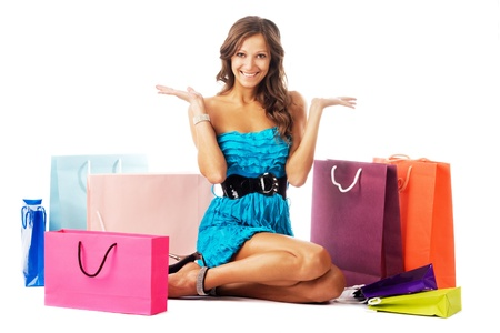 Beautiful excited woman sitting among colorful shopping bags