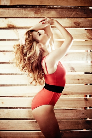 Gorgeous woman in red bodysuit against wooden fence photo