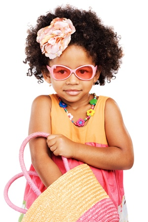 Lovely stylish little girl getting something from her straw bag Stock Photo