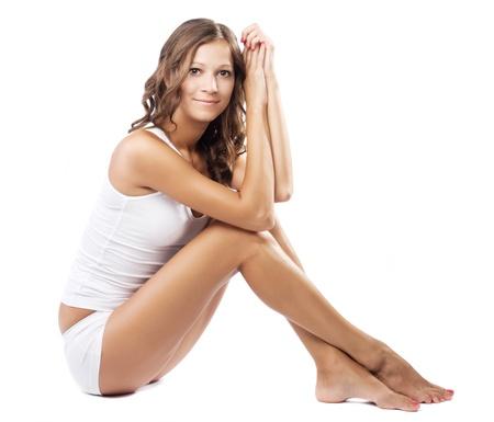 piernas mujer: Joven y bella mujer en ropa interior de algodón en fondo blanco Foto de archivo