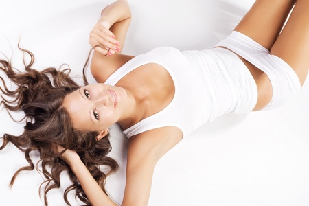 female body: Young beautiful woman in cotton underwear lying on white background