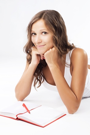 Young beautiful woman with a notebook lying on white background Stock Photo - 17536090
