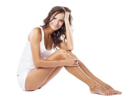 mooie vrouwen: Jonge mooie vrouw in katoenen ondergoed zittend op een witte achtergrond Stockfoto