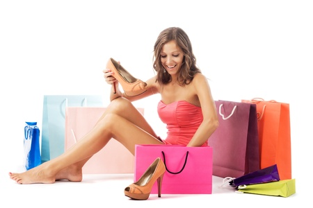 Beautiful excited woman with new shoes sitting among colorful shopping bags