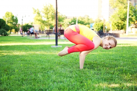 Beautiful sporty woman doing yoga exercise outdoors. Crane pose. photo
