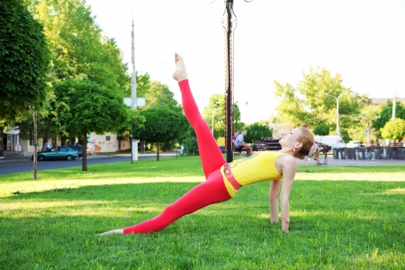 Beautiful sporty woman doing stretching exercise outdoors photo