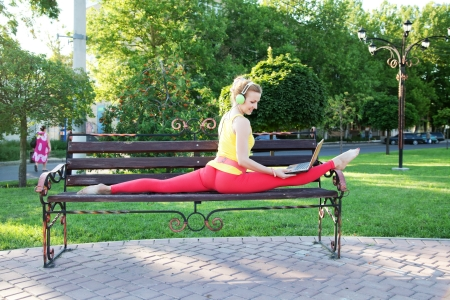 Beautiful sporty woman doing stretching exercise outdoors with laptop photo