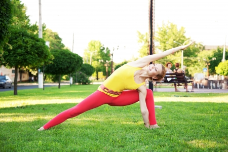 figure out: Beautiful sporty woman doing stretching exercise outdoors