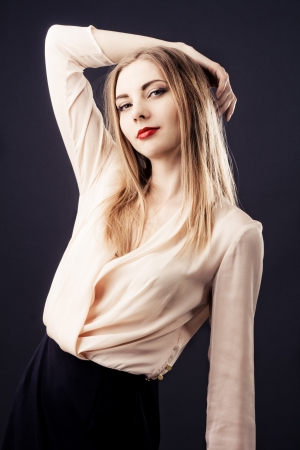 Beautiful woman in chiffon beige blouse against black background  photo