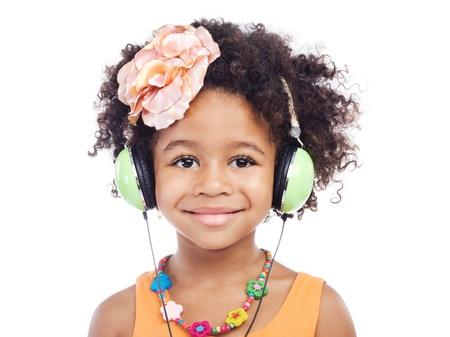 Joyful little girl in big headphones against white background Stock Photo