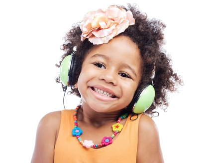Joyful little girl in big headphones against white background photo