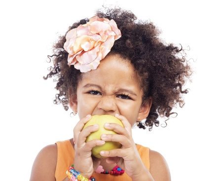 Angry little girl biting an apple, white background photo