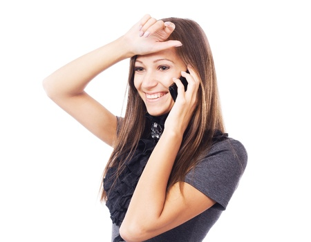 gesticulate: Young joyful woman talking on mobile phone against white background