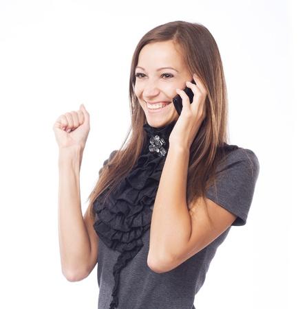 asombro: Mujer alegre joven hablando por teléfono móvil contra el fondo blanco Foto de archivo