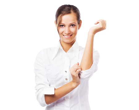 Lovely businesswoman in white shirt turning up sleeves photo