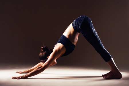 Beautiful sporty woman is working out. Downward-facing dog. Adho Mukha Svanasana. photo