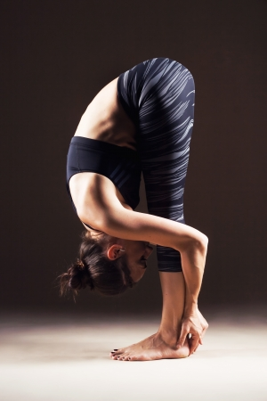 Beautiful sporty woman is working out. Standing forward bend. Uttanasana