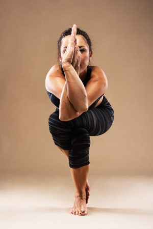 Beautiful sporty woman is working out. Yoga. Eagle pose. Stock Photo