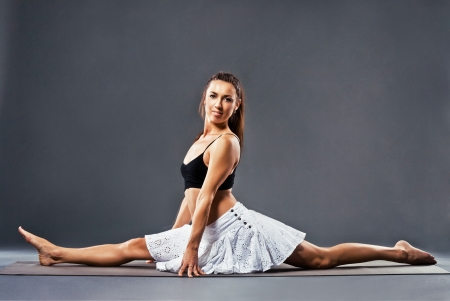 Beautiful sporty woman is working out. The splits. photo