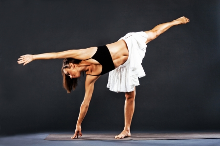 chandrasana: Beautiful sporty woman is working out. Yoga asana. Ardha Chandrasana, Half Moon Pose Stock Photo