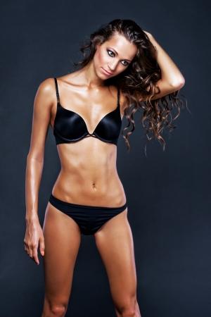 Gorgeous woman in black bikini against dark background Stock Photo - 24002310