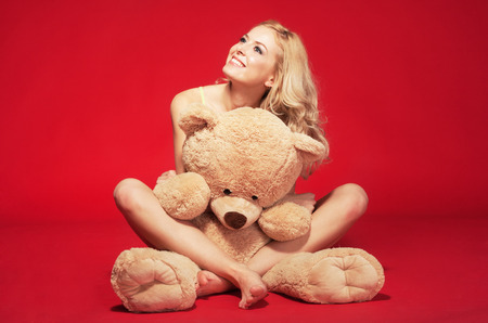 Lovely girl with teddy bear against red background