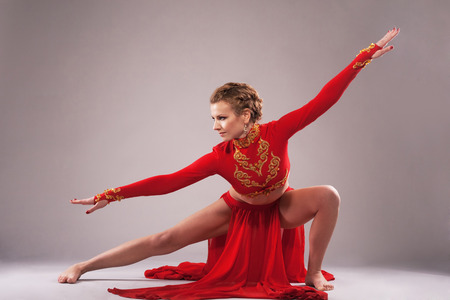 wushu: Studio shot of a gorgeous sporty woman in red clothing. Chinese dancing Stock Photo