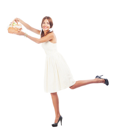 Lovely woman with a basket of cakes against white background photo