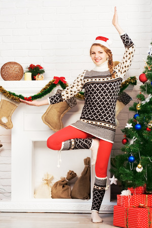 Christmas yoga. Lovely girl doing yoga exercise at home. photo