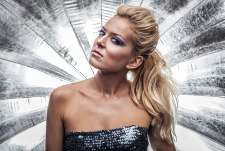 glam rock: Portrait of a gorgeous woman against silver background Stock Photo