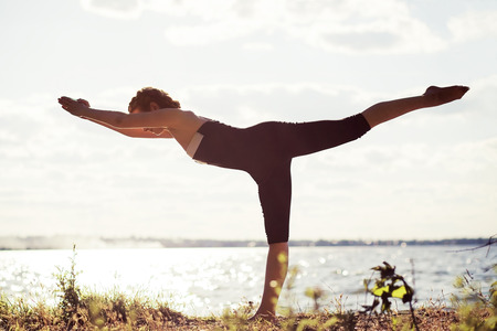 Beautiful sporty woman doing stretching exercise on the river side