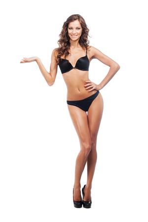 mujer cuerpo completo: Mujer magnífica en negro bikini sosteniendo algo imaginario. Aislado en blanco.