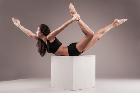 figure out: Beautiful sporty woman is doing yoga exercise on a white cube