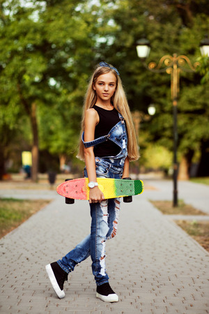 cute teen: Lovely girl with penny board in the park Stock Photo