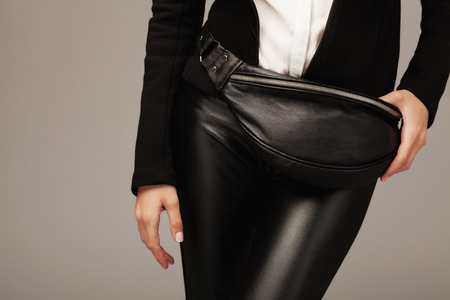 Elegant woman with a black leather fanny pack Imagens - 54871466