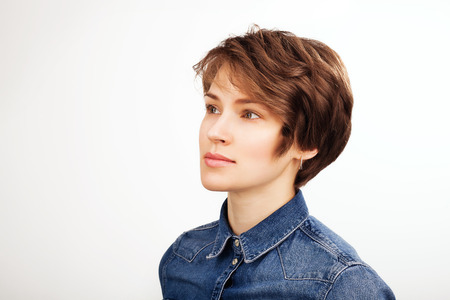 Portrait of inspired beautiful woman in a jean shirt against white background