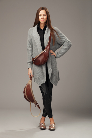 Mujer elegante en chaqueta de punto tejido gris con dos bolsas de cintura de cuero Foto de archivo