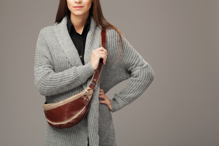 fanny: Elegant woman in gray woven cardigan with a leather fanny pack
