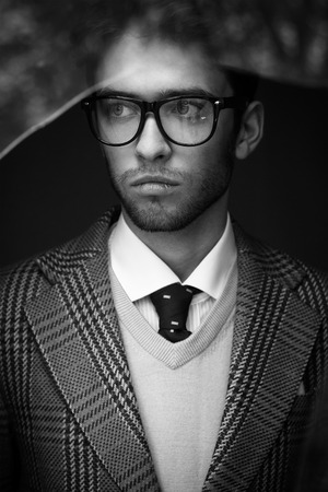 british man: Black and white portrait of a handsome man wearing glasses. British style