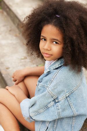 moda ropa: Retrato al aire libre de una niña hermosa que lleva la chaqueta de mezclilla