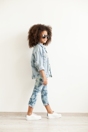 Beautiful stylish little girl in jean clothes