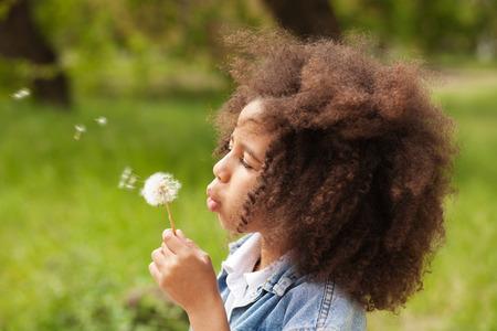 hair curly: niña preciosa que sopla en un diente de león Foto de archivo