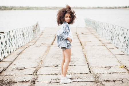 Outdoor portrait of a beautiful stylish little girl