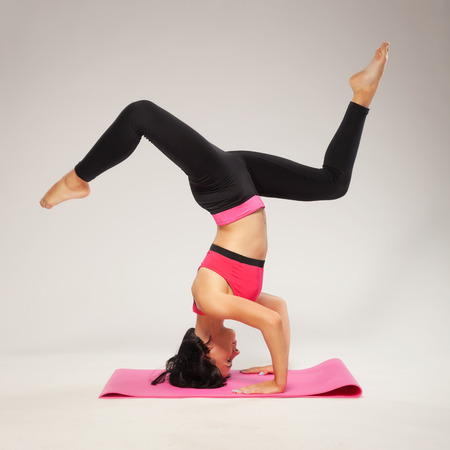headstand: Beautiful sporty woman doing headstand