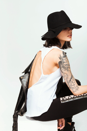 Young beautiful fashion girl in black hat with tattoo on her shoulder Stock Photo